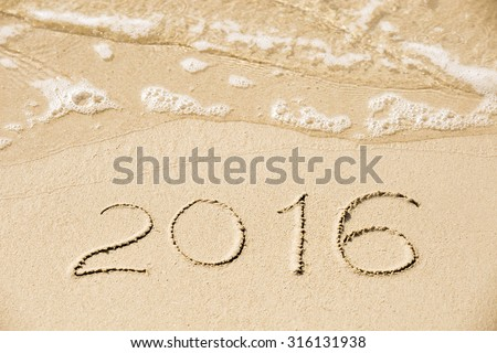 2016 inscription written in the wet yellow beach sand being washed with sea water wave. Concept of celebrating the New Year at some exotic place #316131938