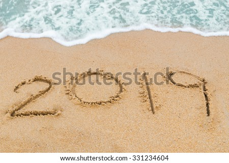 2019 inscription written on sandy beach with wave approaching. #331234604