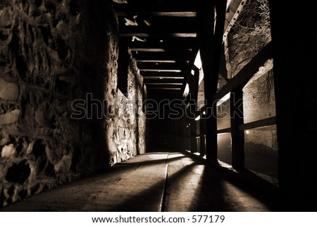 Inside view of a defensive walkway along the outside walls of the city castle of Altena at night. Strong light and shadows give this image a daunting and mysterious atmosphere.
