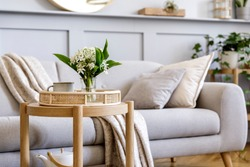 Interior design of scandinavian living room with stylish grey sofa, coffee table, spring flowers, decoration, pillows, plaid, tray and elegant personal accessories in modern home decor.