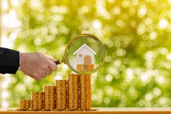 Investor hand hold a magnifier with searching for new home and a stack gold coin growing in the public park, Loan for real estate or saving money for buy a new house to family in the future concept.