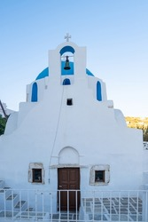 Ios island Cyclade Greece. Agia Aikaterini Christian Orthodox Church. Old traditional whitewashed stonewall temple belfry cross at Chora village Nios summer day.