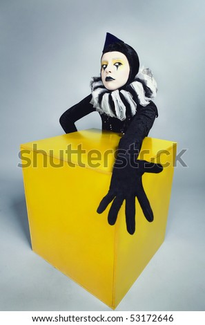 ?ircus fashion mime posing near a yellow square on a grey background. Photo.