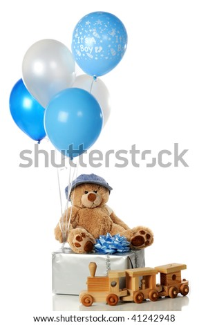 """""""It's a Boy"""" balloon and others with a wrapped gift, Teddy bear in an engineer's cap a toy train.  Isolated on white."""