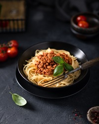 italian spaghetti bolognese in a black bowl , on the background cherry tomatoes