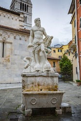 Сityscape. View of Neptune fountain sculpture in Duomo square made by the world famous sculptor Baccio Bandinelli near Carrara cathedral, in Tuscany, Italy.