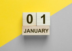 1 January inscription on wooden calendar on background of trendy 2021 colors of yellow and gray. From sad 2020 to happy 2021 concept.