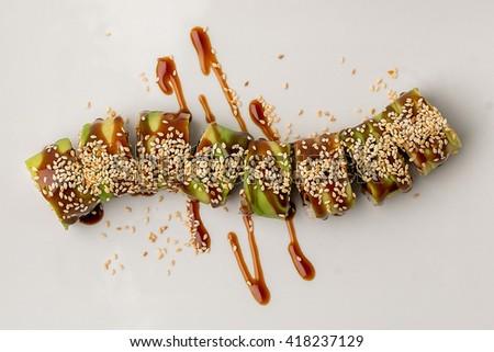 Japanese cuisine, sushi on white background. Sushi roll with salmon and shrimp tempura. Sushi Set and sushi rolls served on stone slate.
