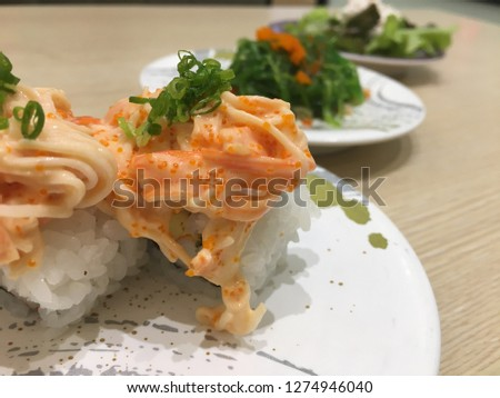 Japanese food pictures placed on a wooden table with sushi, seaweed salad, vegetable salad