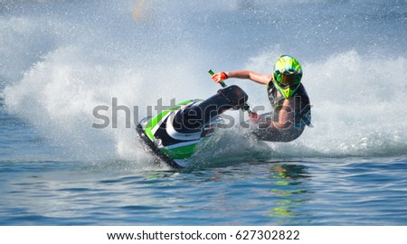 Jet Ski competitor cornering at speed creating at lot of spray. #627302822
