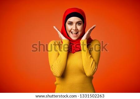 joyful arab woman on orange background
