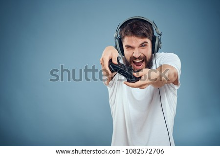 joyful man with headphones on his head with a joystick                              - Shutterstock ID 1082572706