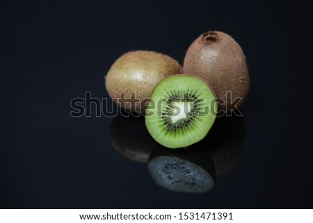 Juicy sectional kiwi with hatching in the mirror on a dark background