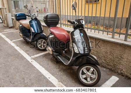 29 June 2017 - Genoa, Italy. Traditional italian scooters - Vespa, parked on the sidewalk in Genoa #683407801