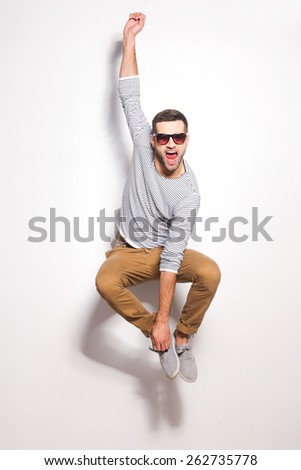 Just having fun. Excited young man jumping in front of the white wall and keeping mouth open