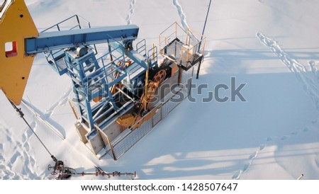 4K Aerial Shot Of A Pump Jack. oil production in the northern region. The equipment operates at the temperature of minus one. #1428507647