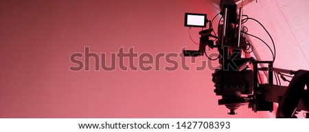 Photo of  4K high definition video camera monitor on tripod or crane in studio and softbox paper and professional lighting equipment for shooting or filming or broadcasting content to advertising commercial