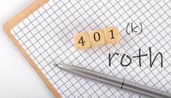 401 K ROTH text concept written on wooden cubes blocks and notebook