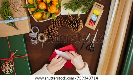 Stock Photo 4K View from Above of Female Hands Putting the Postcard in an Envelope and Writing Christmas Greetings on It