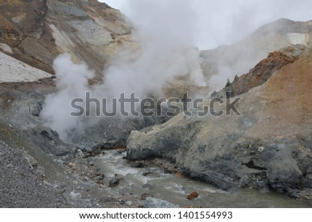 Kamchatka. Mutnovsky volcano. Canyon. Rotate the course of the rushing river. Gases, vapors, sulfur are emitted. Mountains, colored stones, slag, snow. Peaks teeth. The majestic picture.