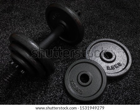 1.25 kg and 2.5 kg weight plates with dumbbell beside on dark background