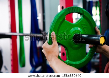 10 kg green weight plates are being put on the barbell To exercise in the class Of functional gyms.