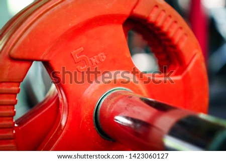 5 kg red weight plates and other colors Was kept neatly in the gym To prepare for exercise In the gym, there are many equipment for functional exercises.