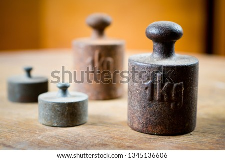 1 kg weights and two smaller in out of focus area. Old rusty measurement steel piece.