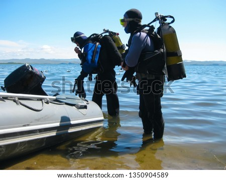 Khuzhir village on Lake Baikal, Russia - July 22, 2012: divers in professional diving equipment preparing to dive at Lake Baikal. Outdoor diving. #1350904589