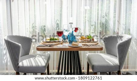 İki   kişilik yemek masası. Kırmızı şarap servis yapılmış. Yan açı Stok fotoğraf ©