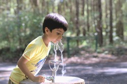 Kid drinking water. Outdoor shot of child drinking water from tap or water bubbler or fountain.