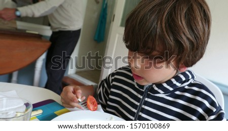 Kid eating lunch Casual young boy eats meal