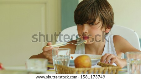 Kid eating lunch Young boy eats pasta