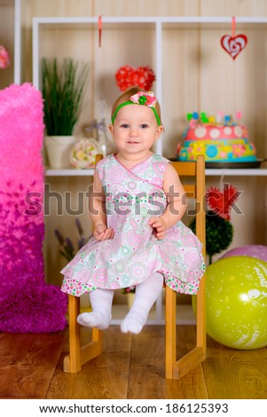 kid in first birthday with colored balloons in the bright room  laughing