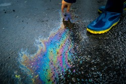 Kid playing touching the spillage and wearing boots. Petrol or petroleum spill on asphalt road. Environmental damage. Toxic oil spill in nature. Rainbow colors from chemicals.