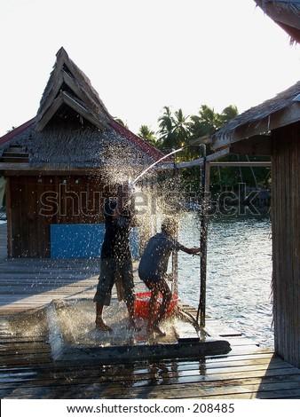 2 kids having fun while taking their shower under bright sunlight