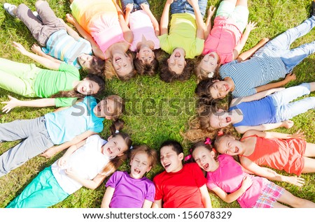 14 kids laying in a circle in the grass with happy faces shoot from above #156078329
