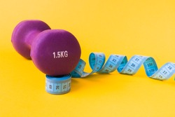 1.5 kilogram purple dumbbell and blue measuring tape on a yellow background, the dumbbell is based on a rolled up tape, copy space, weight loss concept