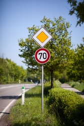 70 kilometres per hour speed sign and priority or right of way yellow diamond on a pole at the side of a rural road or route