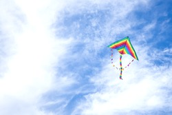 kite in hand on blue sky in sunny weather and wind. Kite flying in summer with copy space.  Freedom. Summer games and fun