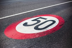 50km/h speed limit sign painted on asphalting road.