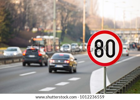 80km/h Speed limit sign with a traffic in the background on a highway full of cars #1012236559