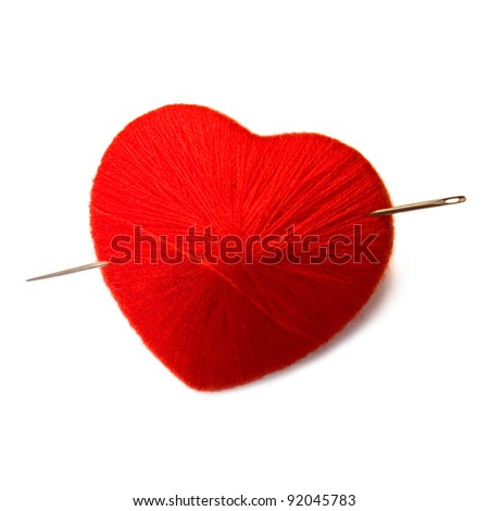 Knit ball in a form of a heart pierced with needle isolated on white background