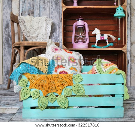 knitted home decorations in wooden box on retro interior background #322517810