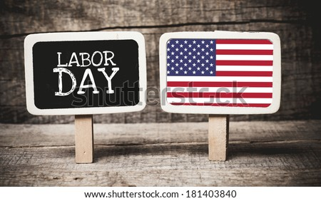 Labor Day written on chalkboard with USA flag on another chalkboard on wooden background