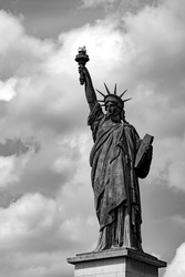 """Lady Liberty"", the smaller original statue on the river Seine in Paris France on a cloudy day seen from a cruise vessel. Idol for the Statue in New York harbour, black and white greyscale."