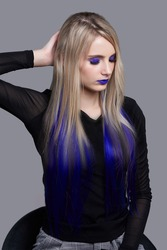 Lady with radiant blue makeup and blue tresses in her long blonde hair is sitting on the black chair. Girl in black blouse and gray plaid trousers put her hand behind the head.