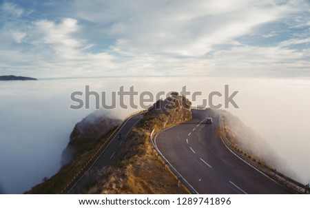 Landscape misty panorama. Fantastic dreamy sunrise on rocky mountains with view into misty valley below. Foggy clouds above forrest. View below to fairy landscape. Foggy forest hillsBeautiful sunset