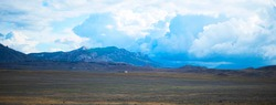 Landscape panorama. Mountains plain sky with clouds. Picturesque area. Copy copy for text.