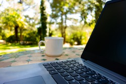Laptop on a mosaic table with a mug beside it, in a country house garden